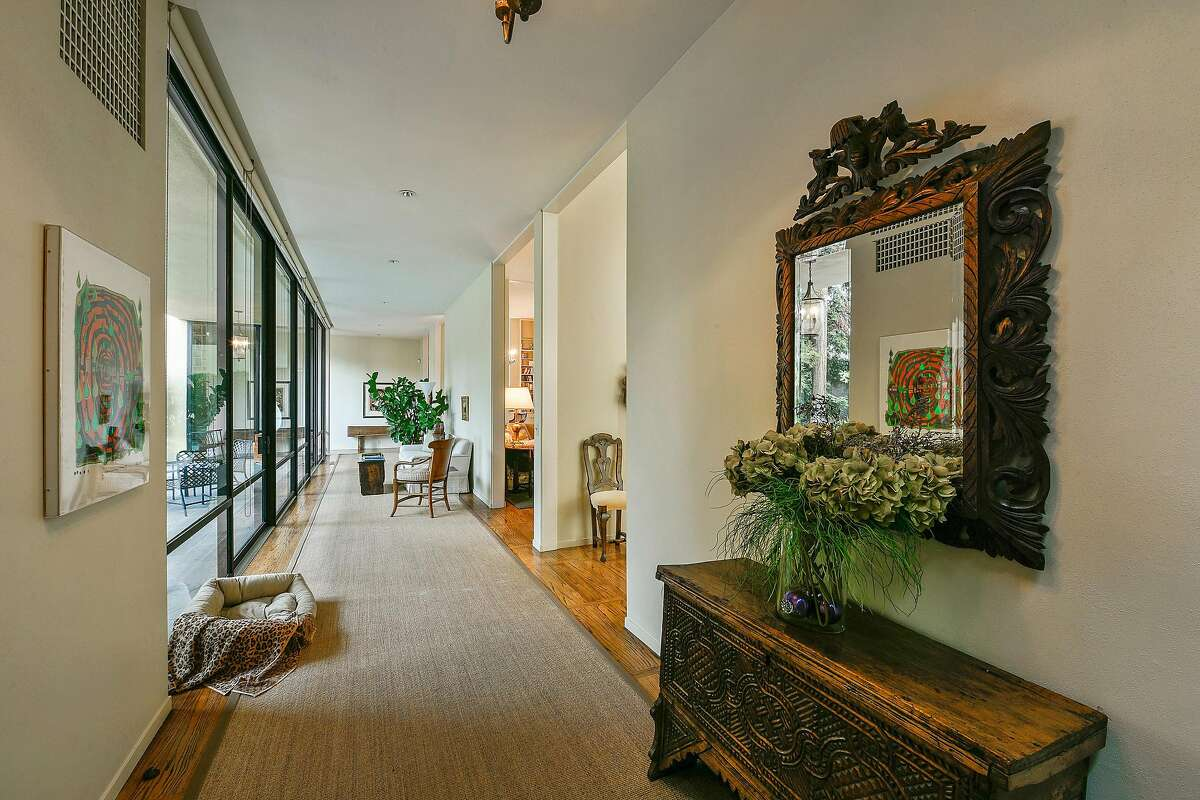 This expansive hallway filters into several public rooms and is flanked by floor-to-ceiling windows facing the rear yard.