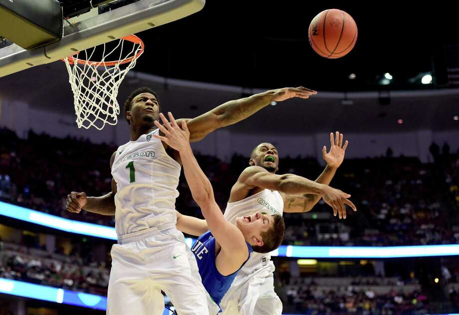 Jordan Bell (1) gives a demonstration of Oregon's superior athleticism as he swats away a shot by Duke's Grayson Allen, center, during the second half. Photo: Harry How, Staff / 2016 Getty Images