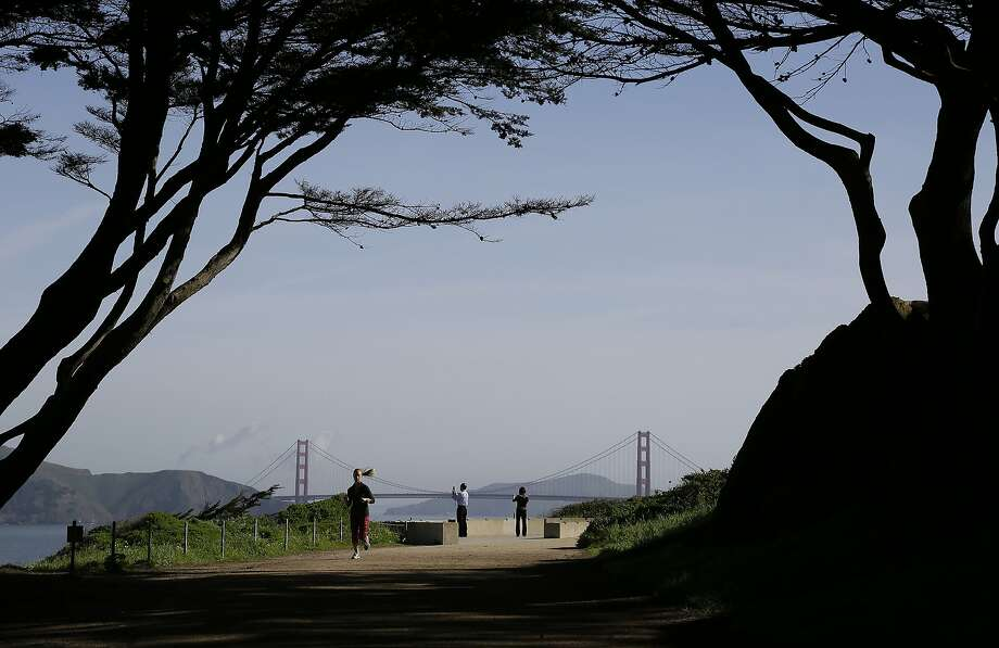 A woman jogs and a couple takes pictures on a trail at Lands End with the Golden Gate Bridge in the background in this file photo from March 24, 2016. Photo: Eric Risberg, AP