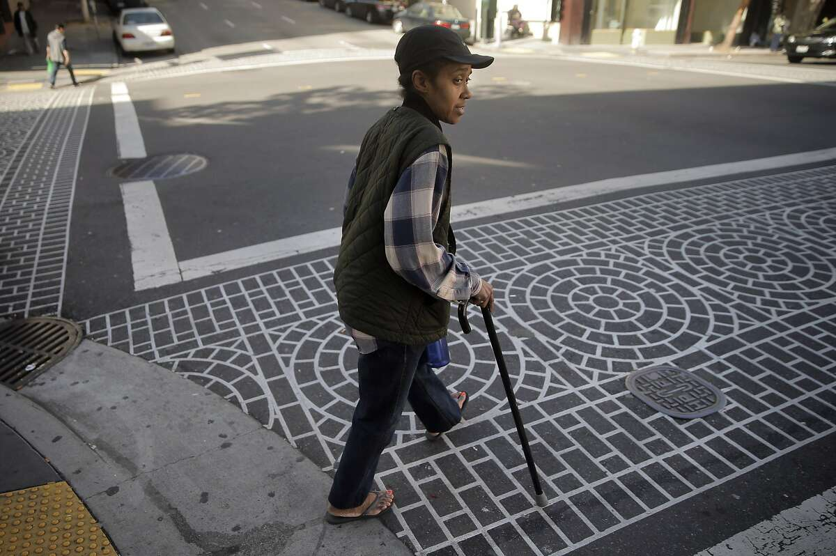 Kim Mays checks the traffic before trying to cross the street at the intersection of Leavenworth Street and Ellis Street in San Francisco, Calif., on Thursday, March 24, 2016. Her cousin, Michael Gilmore was killed at that intersection when hit by a vehicle several weeks prior. Vision Zero is off to a bad start in 2016. So far, at least six pedestrians have been killed in collisions with cars.