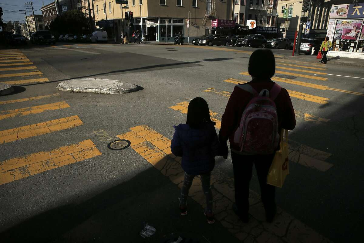 A mother and daughter wait to cross the street at the intersection of Leavenworth Street and Ellis Street in San Francisco, Calif., on Thursday, March 24, 2016. Vision Zero is off to a bad start in 2016. So far, at least six pedestrians have been killed in collisions with cars.