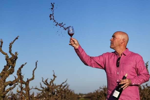 Winemaker Michael McCay tosses wine out of glass while  he swirls it, at TruLux vineyard, in Lodi, California, on Thursday, March 17, 2016.