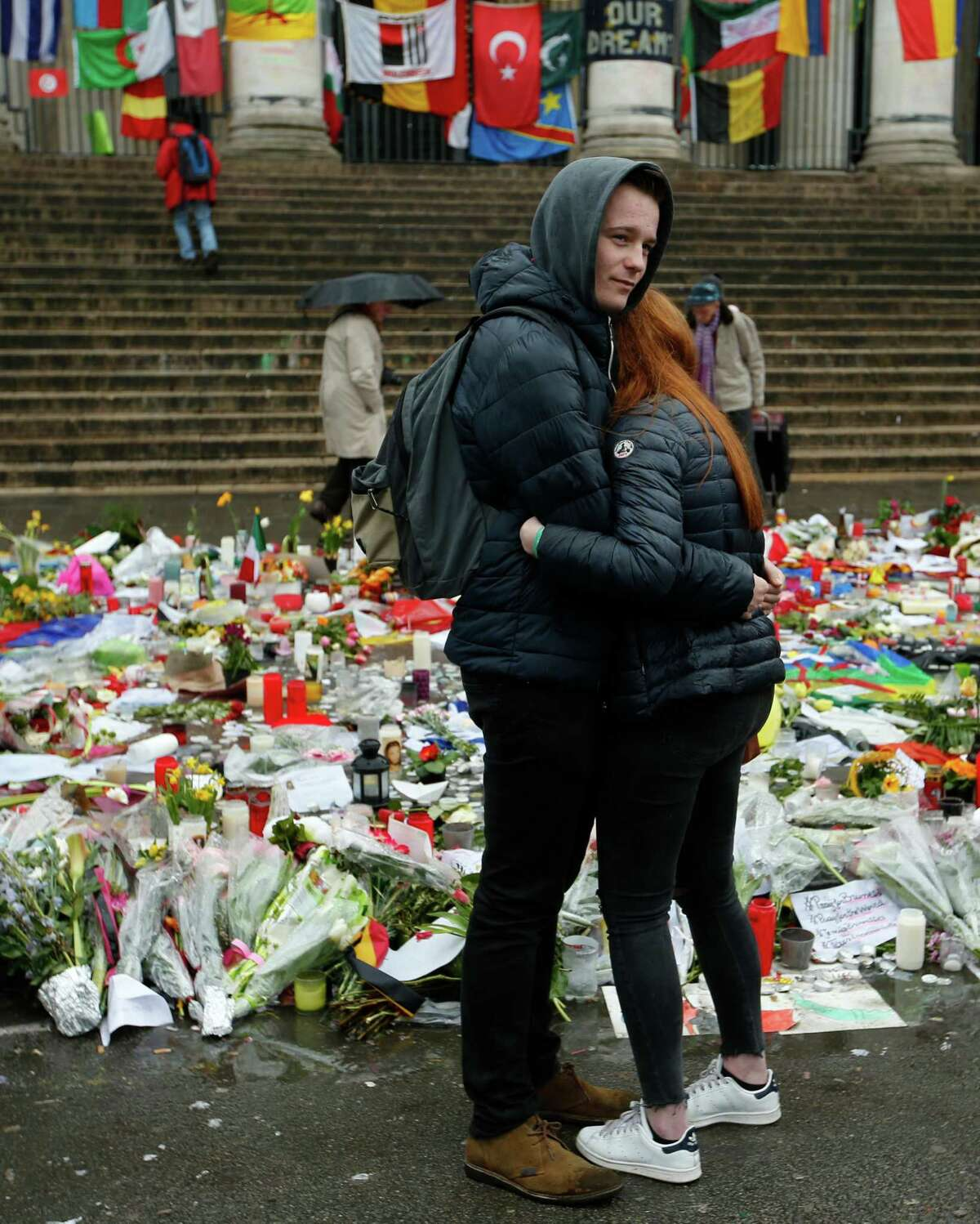 A couple embrace in front of tributes placed in a memorial for victims of the recent attacks on Brussels at the Place de la Bourse in Brussels, Friday, March, 25, 2016. Amid signs that life in Brussels was returning to some sort of normality on the third day of mourning the dead, authorities lowered Belgium's terror-threat level by one notch. However, they said the situation remained grave and another attack is