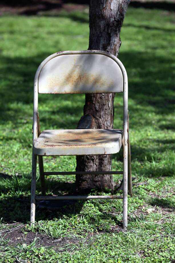 A chair marks a spot Thursday, March 24, 2016 in Brackenridge Park where someone is reserving space for their Easter festivities. Chairs of all kinds begin appearing chained, roped, and simply leaning on just about every possible object in the park as much as a week before Easter as families try to reserve good spots in the park. Photo: San Antonio Express-News / © 2016 San Antonio Express-News