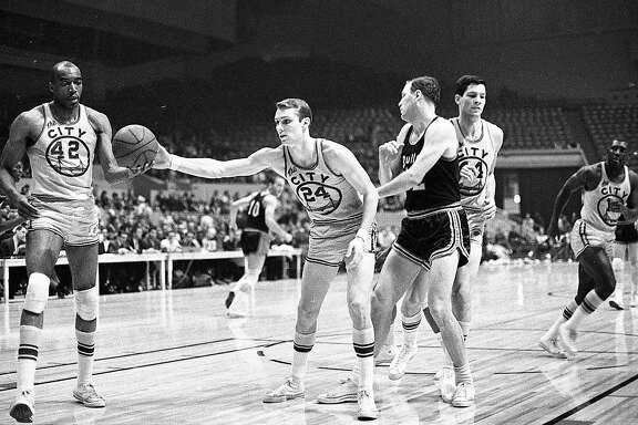 San Francisco Warriors guard Rick Barry hands the ball to Nate Thurmond during a game at the Cow Palace in Daly City against the Bullets. Jan 26, 1967.