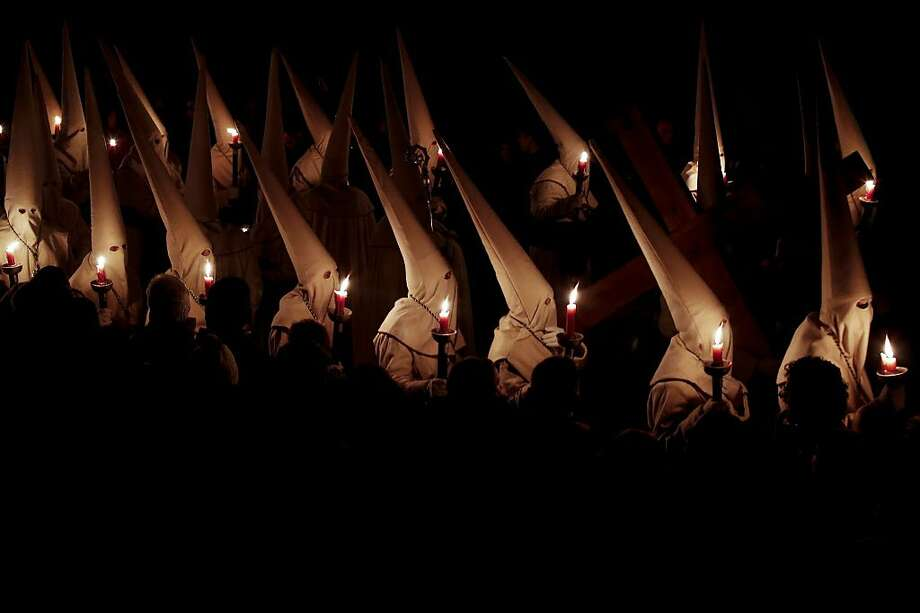 Hooded penitents from the Brotherhood of Jesus Lying hold candles whilst taking part in a procession during Holy Week celebrations in Zamora, Spain, on Thursday, March 24, 2016. Holy processions take place across Spain as Christians gather to celebrate the week leading up to Easter and the death and resurrection of Jesus Christ. Photo: Pau Barrena, Bloomberg