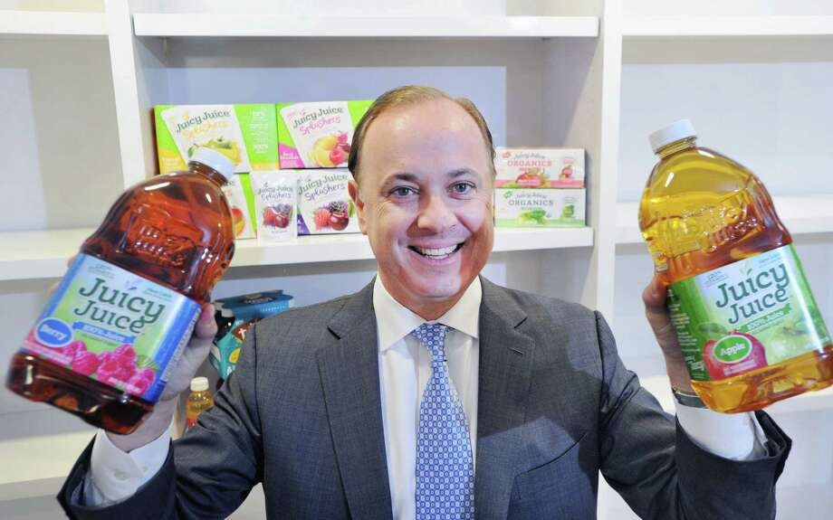 Henk Hartong, chairman & chief executive officer of Brynwood Partners, holds two containers of Juicy Juice at the private equity firm he runs in Greenwich, Conn., Thursday, March 17, 2016. The Juicy Juice brand is one of the products of the Harvest Hill Beverage Company, one of the companies belonging to Brynwood Partners. Photo: Bob Luckey Jr. / Hearst Connecticut Media / Greenwich Time
