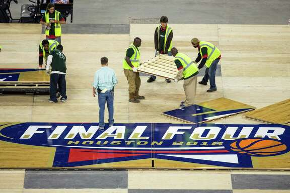 Workers with Connor Sports install the Final Four floor at NRG Stadium on Friday, March 25, 2016, in Houston. The floor is made from Northern Hard Maple, using 397 4-foot by 7-foot panels, weighint approximately 188 pounds each. NRG Stadium will host the NCAA Final Four April 2-4.