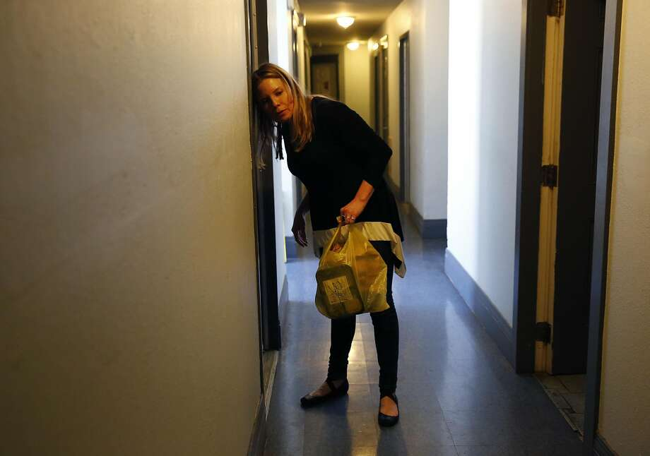 Zendesk employee Lori Gauthier listens at someone's door after knocking while delivering meals for residents through the Meals on Wheels program at the Raman Hotel March 25, 2016 in San Francisco, Calif. Photo: Leah Millis, The Chronicle