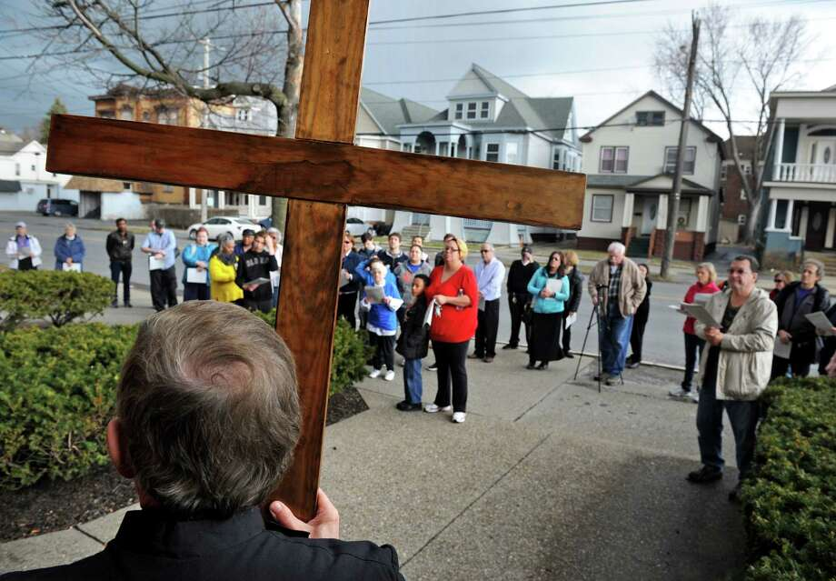 Rev. Peter Schofield carries the cross during the Christ Church Schenectady public Stations of the Cross on Friday, March 25, 2016, in Schenectady, N.Y. (Michael P. Farrell/Times Union) Photo: Michael P. Farrell / 10035914A