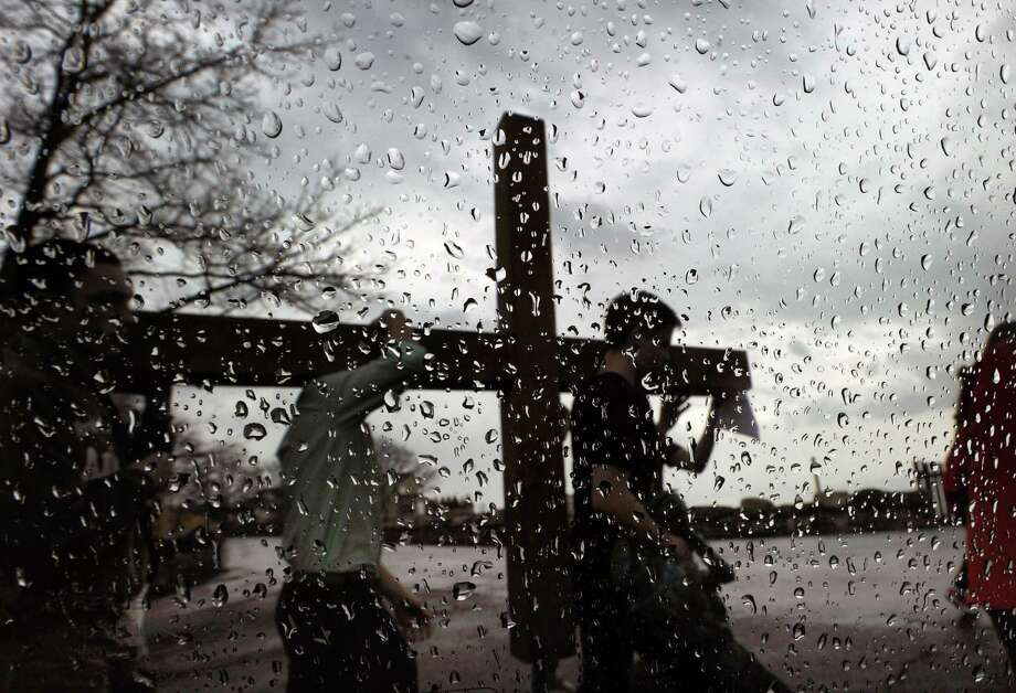 "Seen through raindrops on a car window, the First Congregational Church of Greenwich youth group carries a large wooden cross on Shore Road, Good Friday afternoon, in Old Greenwich, Conn., March 25, 2016. The cross was carried by alternating members of the youth group from the First Congregational Church in Old Greenwich to Greenwich Point, a distance of a little more than 2 miles, where it will be used for the sunrise service on Easter Sunday morning. Donald Haviland, a youth group minister at the church who was supervising the event, said about 15-20 youth group members took part. Youth group member Daniel Lepoutre, 16, said about the cross walk, ""we wanted to feel what Jesus felt when he carried the cross by himself way back when on Good Friday."" Photo: Bob Luckey Jr. / Hearst Connecticut Media / Greenwich Time"