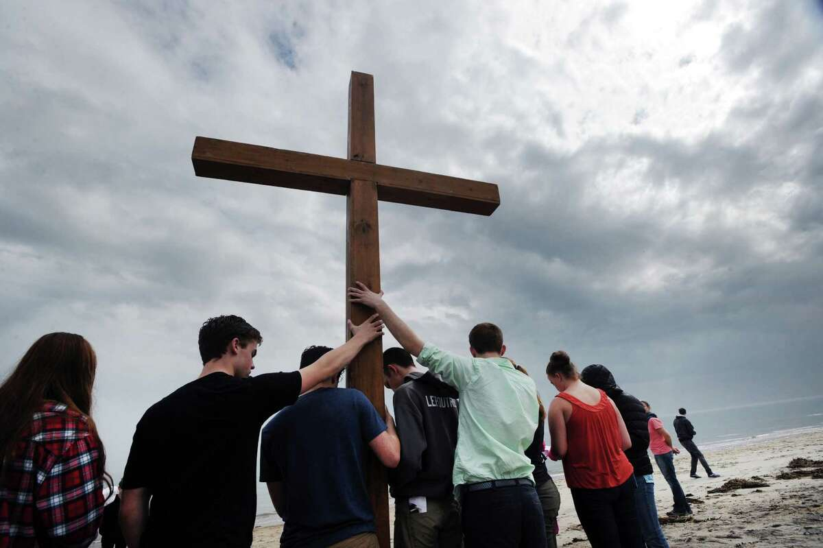 The First Congregational Church of Greenwich youth group prays after placing a wooden cross into the sand on Greenwich Point beach, Good Friday afternoon, in Old Greenwich, Conn., March 25, 2016. The cross was carried by alternating members of the youth group from the First Congregational Church in Old Greenwich to Greenwich Point, a distance of a little more than 2 miles, where it will be used for the sunrise service on Easter Sunday morning. Donald Haviland, pictured here at right, a youth group minister at the church who was supervising the event, said about 15-20 youth group members took part. Youth group member Daniel Lepoutre, 16, said about the cross walk,