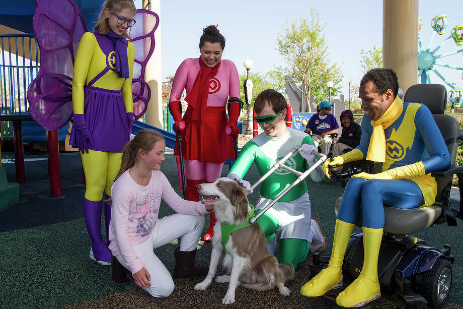 Brooke Barnwell, 8, pets Uno, X-Ray's seeing eye dog at Morgan's Wonderland Saturday, March 19, 2016. X-Ray (Taylor James Johnson) is one of the new superheroes at Morgan's Wonderland along with (left to right) Rachel Laven as Morgan, Marisa Flores as Jette and Andrew Jacobi Jeter as Rocket. Photo: Alma E. Hernandez, For The San Antonio Express News / Alma E. Hernandez / For The San Antonio Express News