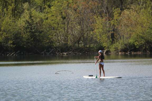 Kristi Johnson, of Lodi, navigates down the Lower Mokelumne River on a stand-up paddle board.