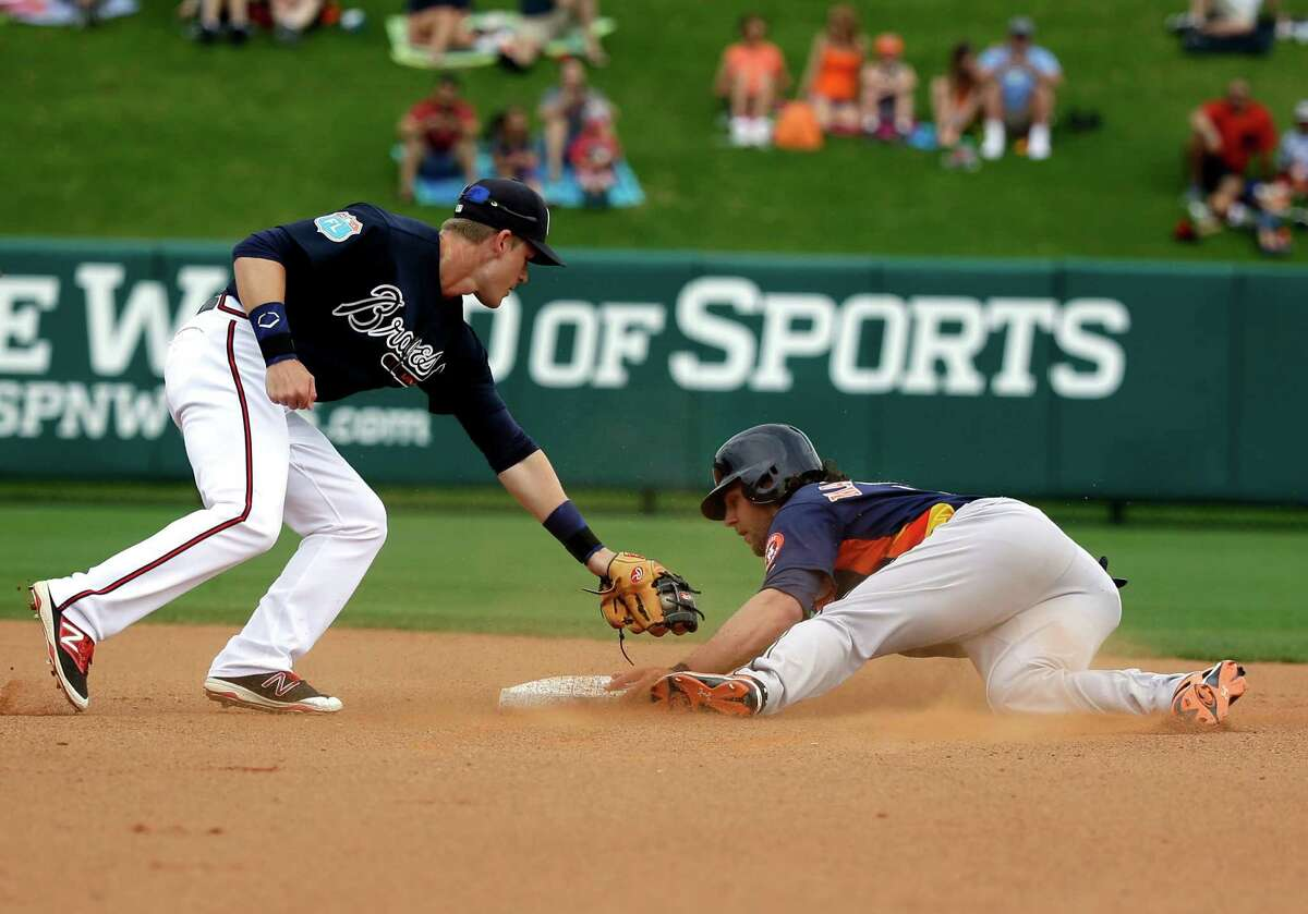 Houston Astros' Jake Marisnick, right, steals second base as he avoids the tag by Atlanta Braves infielder Gordon Beckham in the fourth inning of a spring training baseball game, Friday, March 25, 2016, in Kissimmee, Fla.