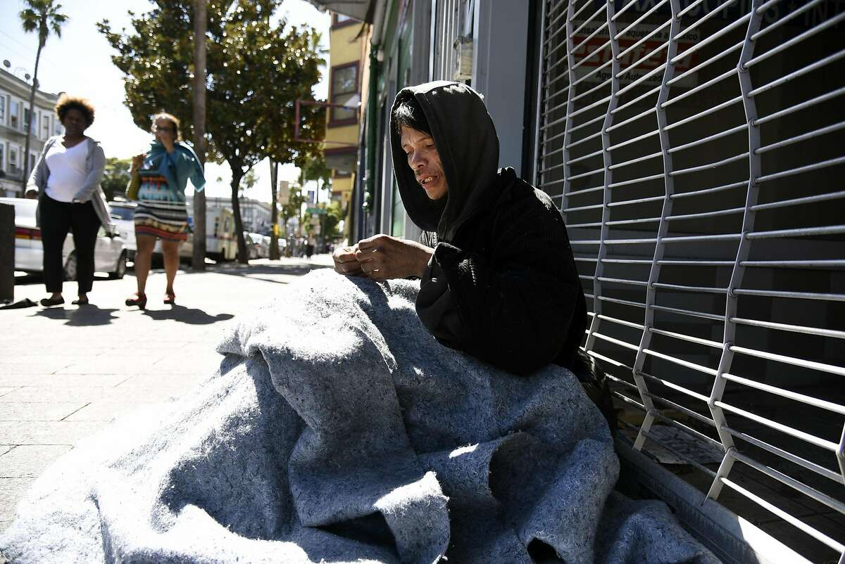 Homeless person Sandy Nung sits on the ground a fews doors down from a building at 1930 Mission Street where nuns of the Fraternite Notre Dame Mary of Nazareth Soup Kitchen is to relocate after they were evicted from their former location, in San Francisco, CA Friday, March 25, 2015.