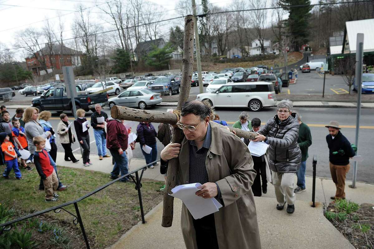 Fred Scipione and Cheryn Kwasnik, carry the cross into St. Thomas Episcopal Church in Bethel during a Good Friday observance. Christian churches in Bethel joined together in an ecumenical Stations of the Cross service in observance of Good Friday, March 25, 2016. The day marks the crucification of Jesus Christ, three days before Easter.