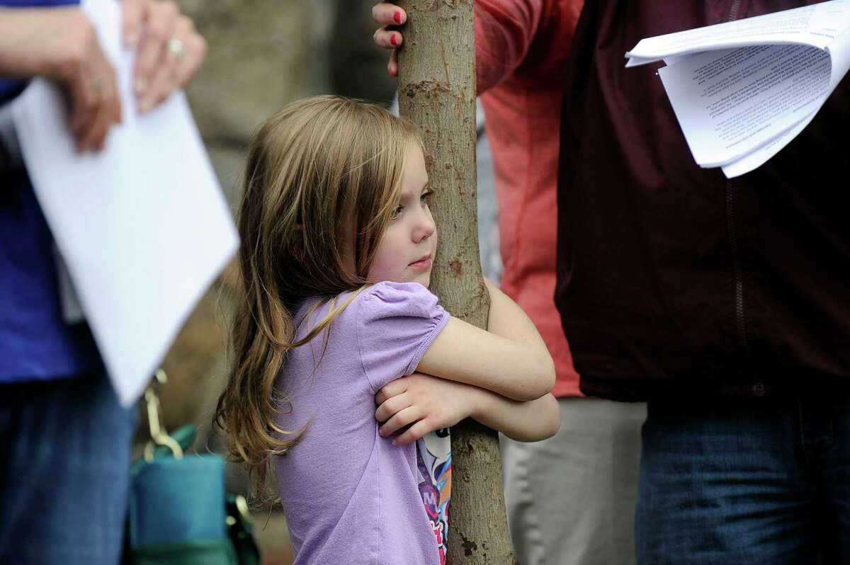 Hailey Mott, 4, of Bethel, hugs the cross during a Good Friday service Friday, March 25, 2016. Christian churches in Bethel joined together in an ecumenical Stations of the Cross service in observance of Good Friday, March 25, 2016. The day marks the crucification of Jesus Christ, three days before Easter.
