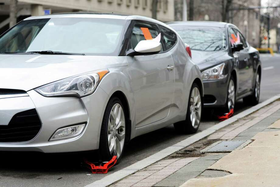 Cars on State Street in Bridgeport are booted with wheel locks on Thursday. Photo: Cathy Zuraw / Hearst Connecticut Media / Connecticut Post