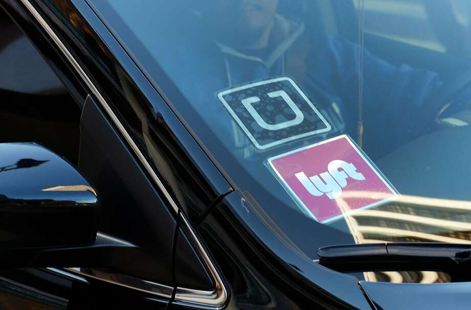In this Tuesday, Jan. 12, 2016 file photo, a driver displaying Lyft and Uber stickers on his front windshield drops off a passenger in downtown Los Angeles, Calif. Passengers arriving at Los Angeles International Airport will be allowed to leave in an UberX car starting Thursday, Jan. 21. (AP Photo/Richard Vogel, File) Photo: Richard Vogel, Associated Press