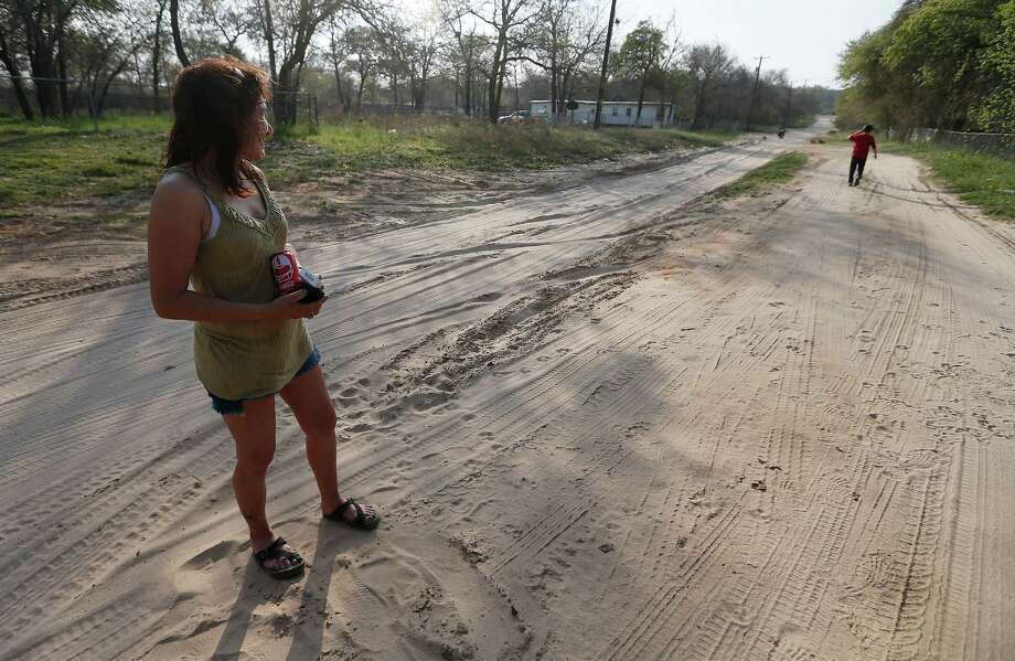 Laura Meyers watches her son walk down Black Willow Street to meet a friend on March 8. Residents and vehicles use Black Willow Street in South Bexar County on a daily basis despite the conditions along the unpaved road. Bexar County will be taking over the maintenance of the road in a multi-year program likely to start next year. Photo: Kin Man Hui /San Antonio Express-News / ©2016 San Antonio Express-News