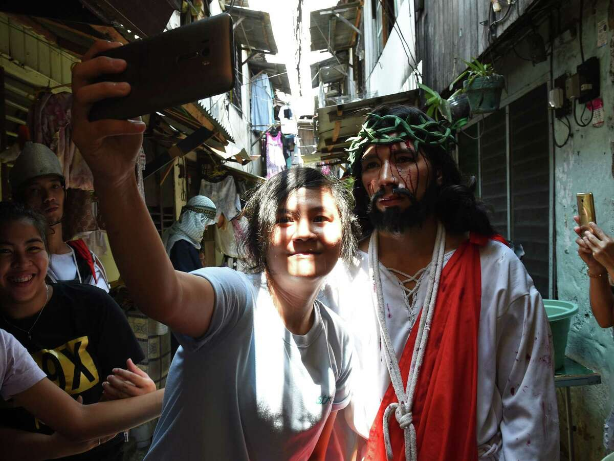 A spectator takes a selfie with an actor playing the role of Jesus during the reenactment of the suffering and crucifixion of Jesus in a street play as part of Lenten observance during Holy Week in Manila on March 24, 2016, ahead of Easter. Christian believers around the world mark the Holy Week of Easter in celebration of the crucifixion and resurrection of Jesus Christ. / AFP / TED ALJIBE