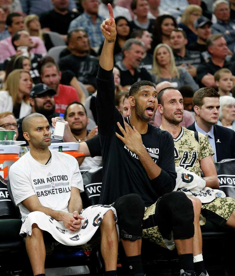 Spurs' Tim Duncan (center) roots for the guys on the floor while seated with teammate Tony Parker (left) and Manu Ginobili (right) during the game against the Miami Heat at the AT&T Center on March 23, 2016. Photo: Kin Man Hui /San Antonio Express-News / ©2016 San Antonio Express-News