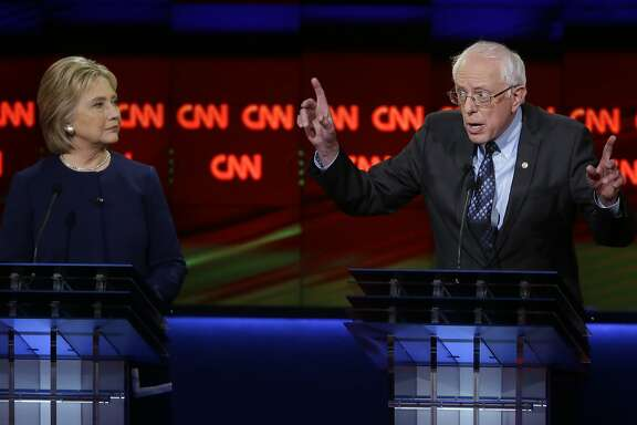 Democratic presidential candidate, Sen. Bernie Sanders, I-Vt., right, argues a point as Hillary Clinton listens during a Democratic presidential primary debate at the University of Michigan-Flint, Sunday, March 6, 2016, in Flint, Mich.  (AP Photo/Carlos Osorio)