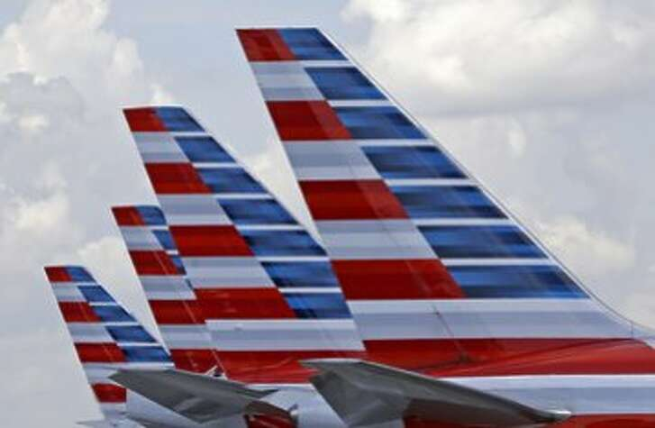 FILE - This photo July 17, 2015, photo shows the tails of four American Airlines passenger planes parked at Miami International Airport, in Miami.  American Airlines, on Wednesday, Dec. 9, 2015, says it will start selling �premium economy� service on international flights, with leather seats, entertainment systems and meals. The seats will cost more than coach but less than business class, although American isn�t stating prices. (AP Photo/Alan Diaz, File)