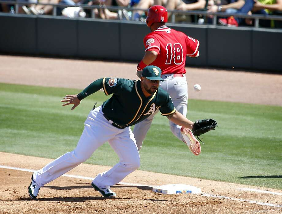 Los Angeles Angels Geovany Soto (18) is safe at first as Oakland A's Yonder Alonso can't handle the throw during the first inning of a spring training baseball game, Friday, March 25, 2016, in Mesa, Ariz. Alonso was charged with an error on the play. (AP Photo/Matt York) Photo: Matt York, AP