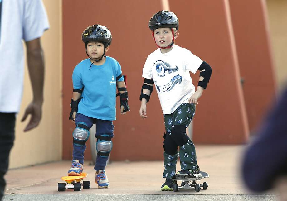 Jinwon Lee (left) and Travis Schrader, both 5, learn how to skateboard in one of the city's offerings. Photo: Liz Hafalia, The Chronicle