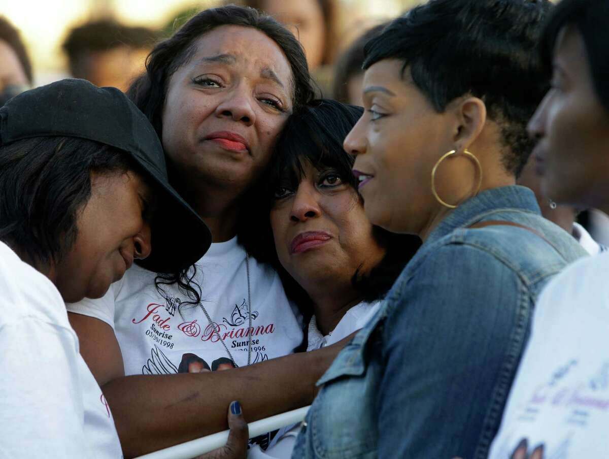Stacey Robinson, second from left, is consoled on Friday as she attends a memorial at Glenshire Park, 12100 Riceville School Road, for her two daughters, Jade and Brianna, who were killed in a crash on Sunday.