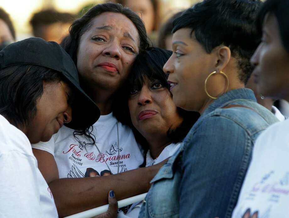 Stacey Robinson, second from left, is consoled on Friday as she attends a memorial at Glenshire Park, 12100 Riceville School Road, for her two daughters, Jade and Brianna, who were killed in a crash on Sunday. Photo: Melissa Phillip, Houston Chronicle / © 2016 Houston Chronicle