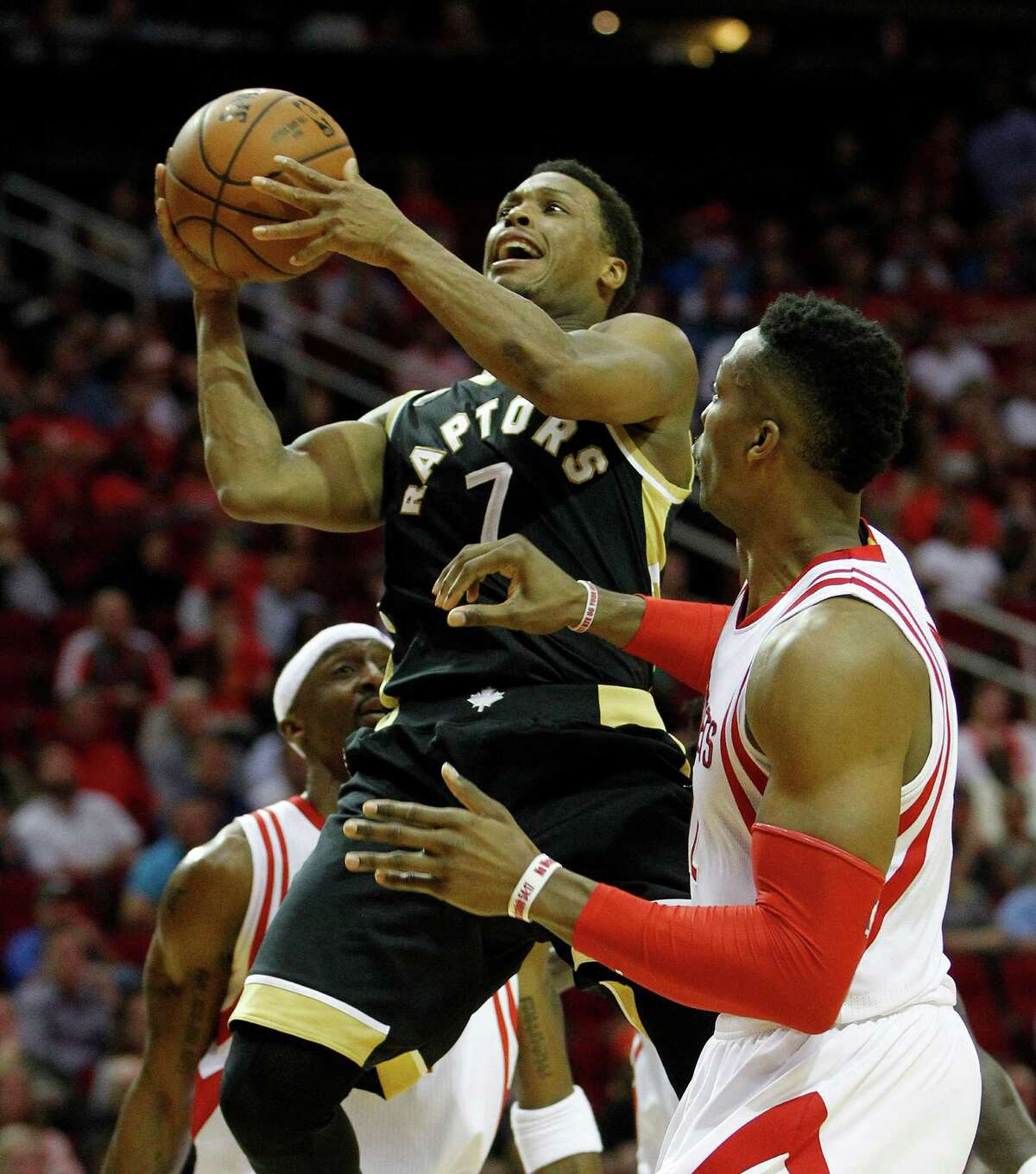 Toronto Raptors guard Kyle Lowry (7) goes up for a basket against Houston Rockets center Dwight Howard (12) during the second half of an NBA basketball game at Toyota Center, Friday, March 25, 2016. Rockets won 112-109.