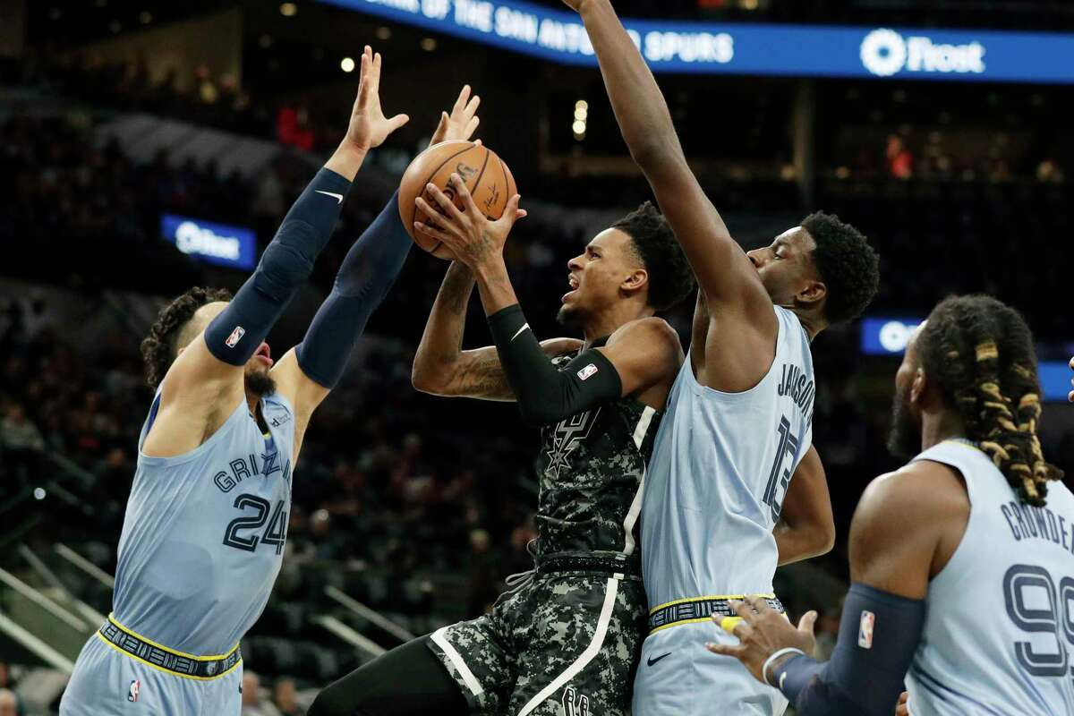 San Antonio Spurs guard Dejounte Murray (5) shoots between Memphis Grizzlies guard Dillon Brooks (24) and forward Jaren Jackson Jr. (13) during the first half of an NBA basketball game, in San Antonio, Monday, Nov. 11, 2019. (AP Photo/Eric Gay)