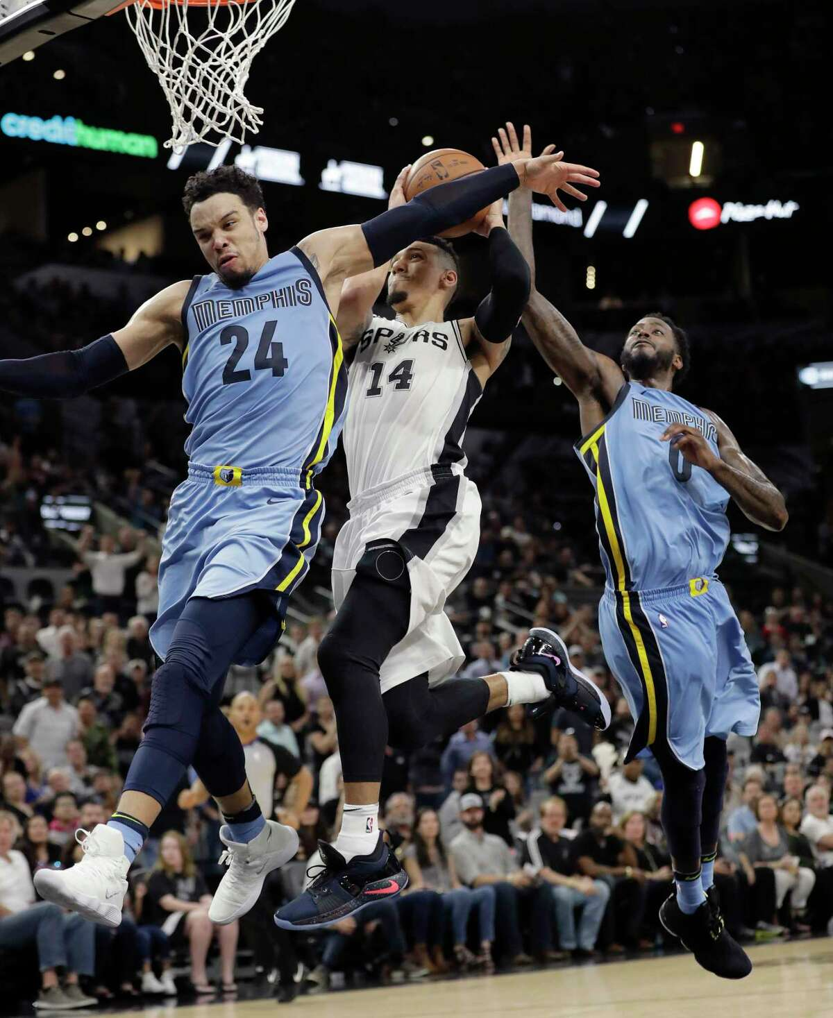 San Antonio Spurs guard Danny Green (14) drives to the basket between Memphis Grizzlies defenders Dillon Brooks (24) and JaMychal Green (0) during the second half of an NBA basketball game, Monday, March 5, 2018, in San Antonio. (AP Photo/Eric Gay)