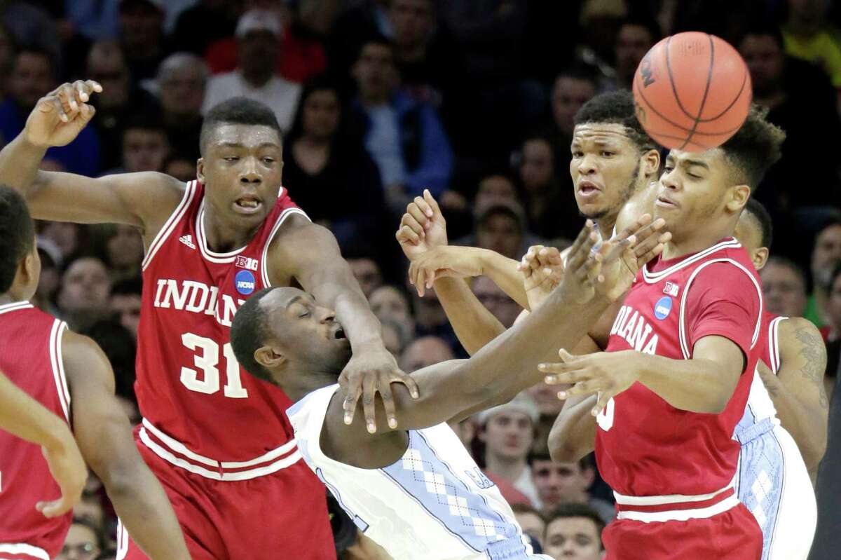 Indiana's Thomas Bryant (31) collides with North Carolina's Theo Pinson as Indiana's Juwan Morgan, right, looks on in the first half during a Sweet 16 matchup in the NCAA Tournament's East region at the Wells Fargo Center in Philadelphia on Friday, March 25, 2016.