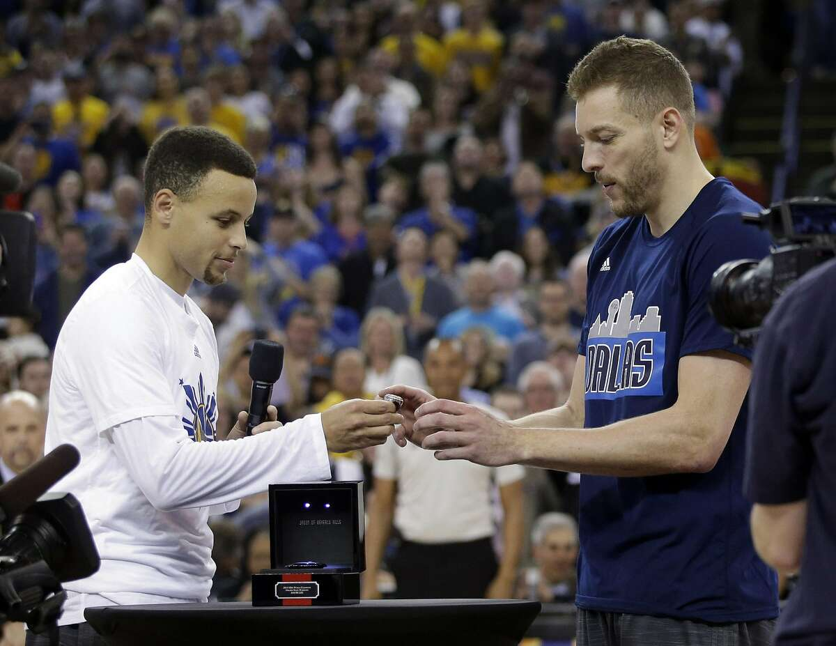 Golden State Warriors' Stephen Curry, left, presents Dallas Mavericks' David Lee with a 2015 World Championship ring during a pre game ceremony before NBA basketball game Friday, March 25, 2016, in Oakland, Calif. (AP Photo/Marcio Jose Sanchez)
