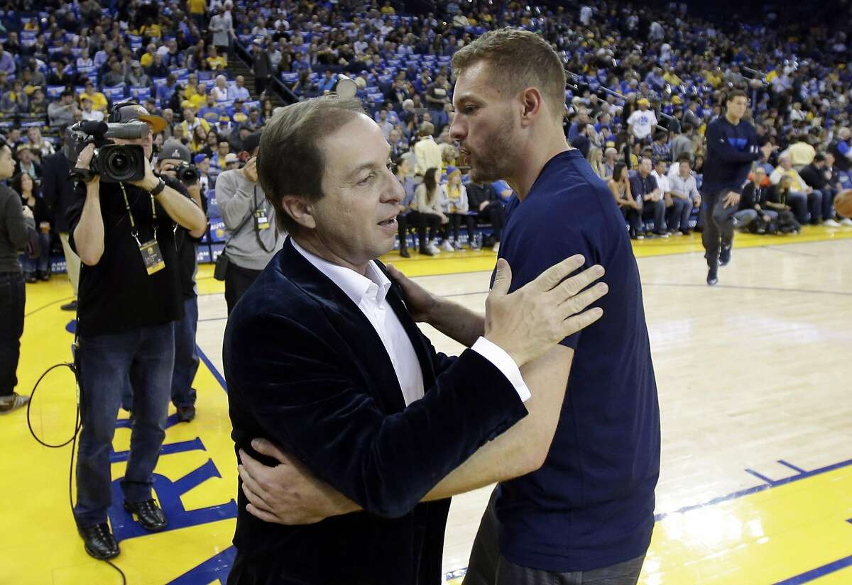 Dallas Mavericks' David Lee, right, gets a hug from Golden State Warriors owner Joe Lacob before an NBA basketball game Friday, March 25, 2016, in Oakland, Calif. Lee was receiving his World Championship ring for being a member of the 2015 Warriors NBA championship team. (AP Photo/Marcio Jose Sanchez)