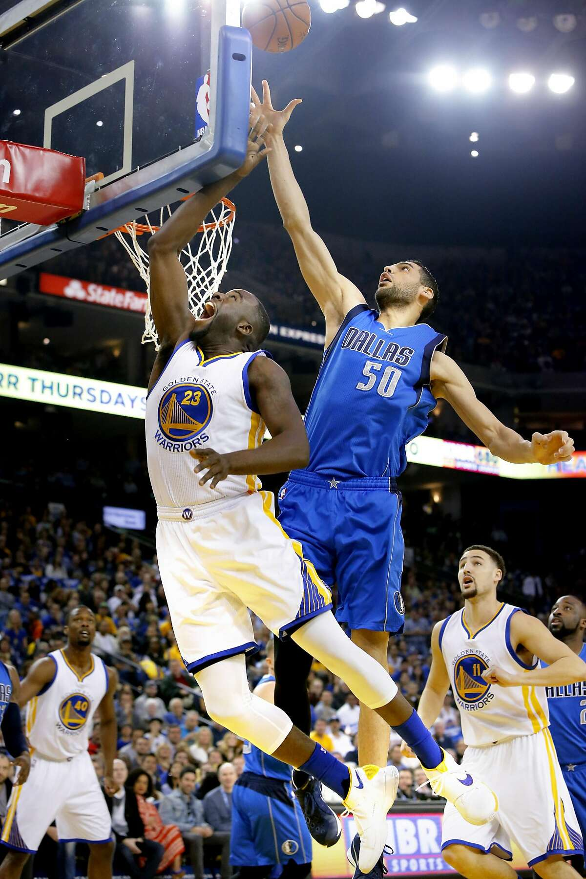 Warriors' Draymond Green, 23 drives past the Mavericks' Salah Mejri, 50 during the first half, as the Golden State Warriors take on the Dallas Mavericks at Oracle Arena in Oakland, California, on Fri. March 25, 2016.