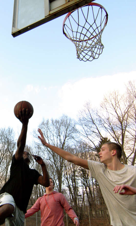 William Melvin, of Trumbull, lays up the ball as Matt Shea, also from Trumbull, goes to block, as they play some basketball with friends at Island Brook Park in Trumbul, Conn. on Tuesday February 7, 2012. On March 7, the Senior/Community Center Study and Planning Committee revealed that the park was not a viable location for a new senior center because of its status as a 100-year flood zone. Photo: Christian Abraham / Christian Abraham / Connecticut Post