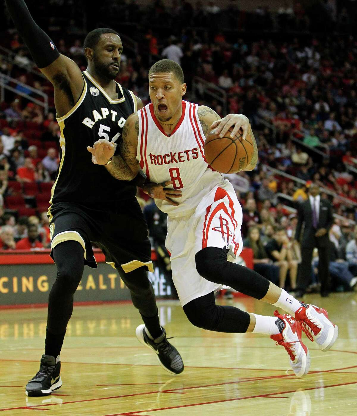 Rockets forward Michael Beasley, right, drives to the basket against Raptors forward Patrick Patterson. Beasley had 21 points, going 9-for-12.