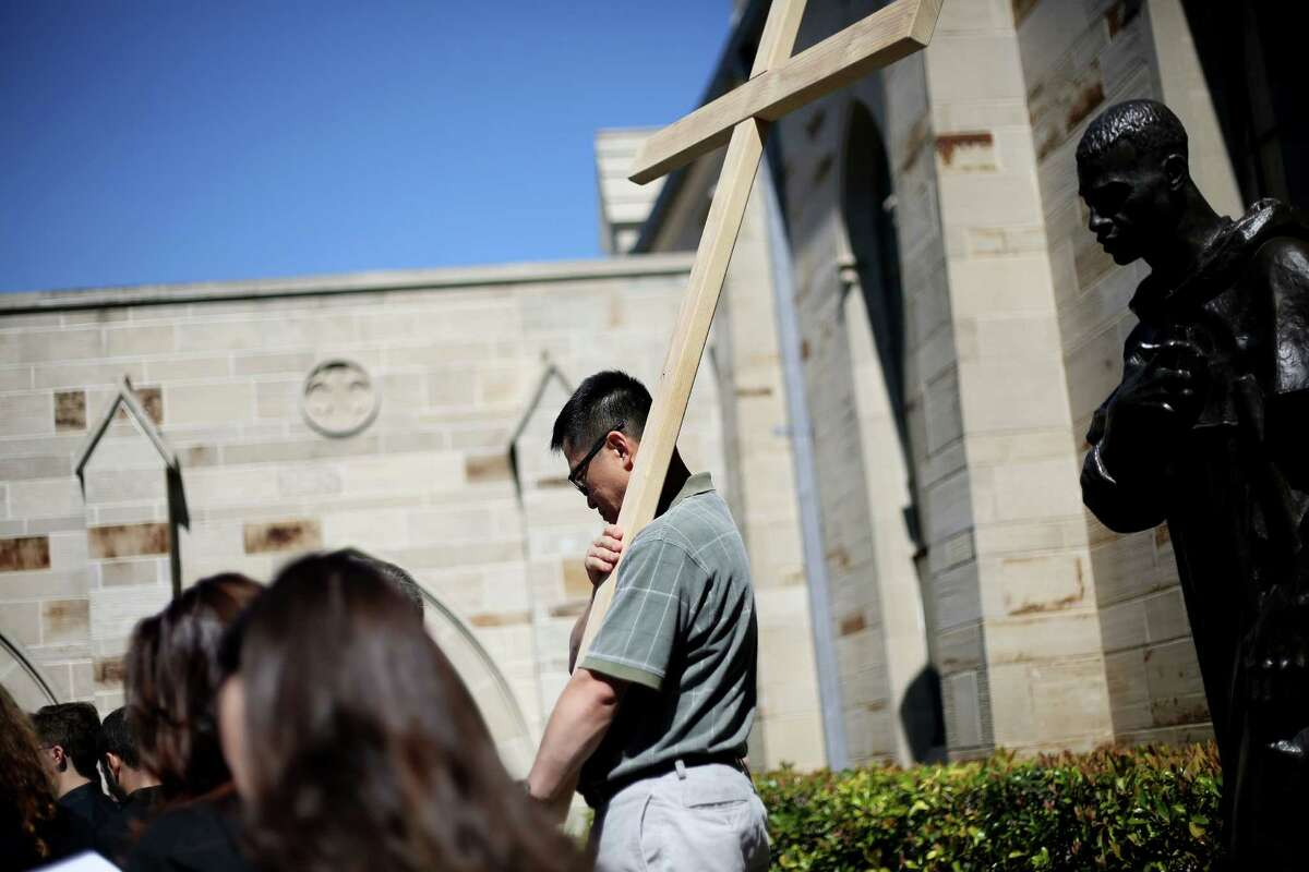 Khoi Nguyen holds the cross at the courtyard of the Holy Rosary Cathedral as part of the Communion and Liberations Way of the Cross program for Good Friday on Friday, March 25, 2016, in Houston.