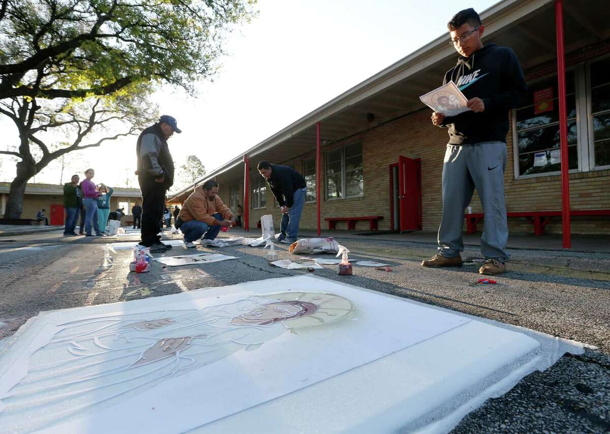 Anthony Esquivel, 15, works on a carpet, made of salt and coloring, at Holy Ghost Catholic Church Friday, March 25, 2016, in Houston. People will walk over the carpets, destroying them, in a live reenactment of the stations of the cross.