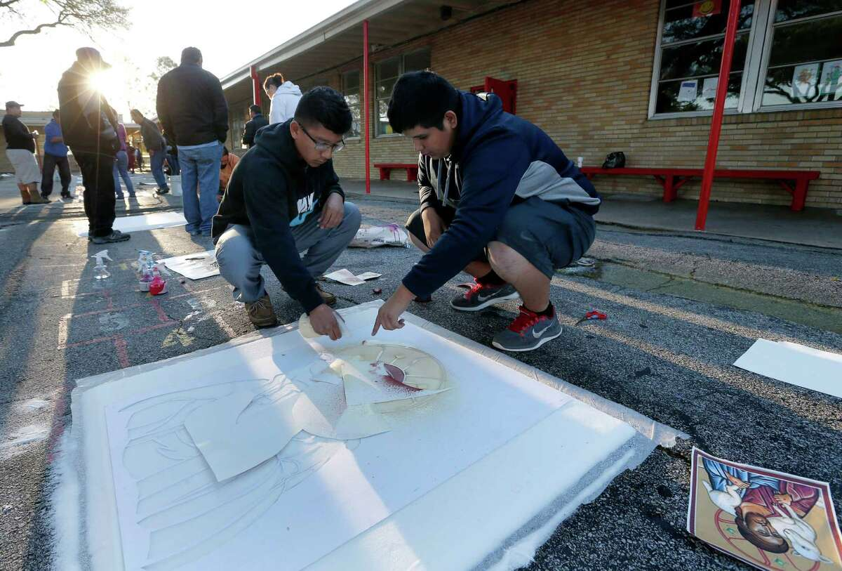 Eric Esquivel, 17, right, and his brother Anthony, 15, color a design into a carpet, made from salt, at Holy Ghost Catholic Church Friday, March 25, 2016, in Houston. People will walk over the carpets, destroying them, in a live reenactment of the stations of the cross.