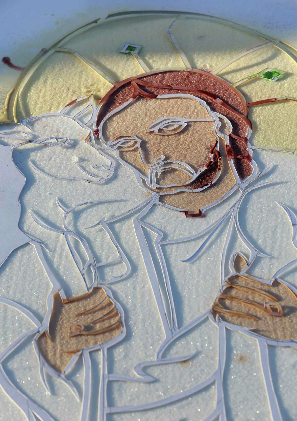 A carpet, made from salt and coloring, is seen at Holy Ghost Catholic Church Friday, March 25, 2016, in Houston. People will walk over the carpets, destroying them, in a live reenactment of the stations of the cross.