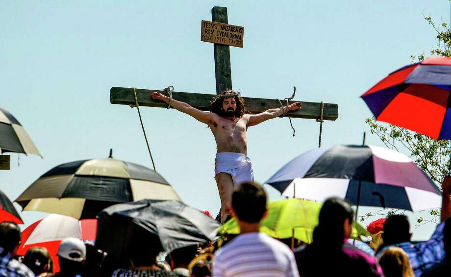 About 2000 people watch as an actor playing Jesus is lifted up on the cross during the procession of the Stations of the Cross at the St. Elizabeth Ann Seton Catholic Church and Schools Friday, March 25, 2016 in Houston. Photo: Michael Ciaglo, Houston Chronicle / © 2016  Houston Chronicle