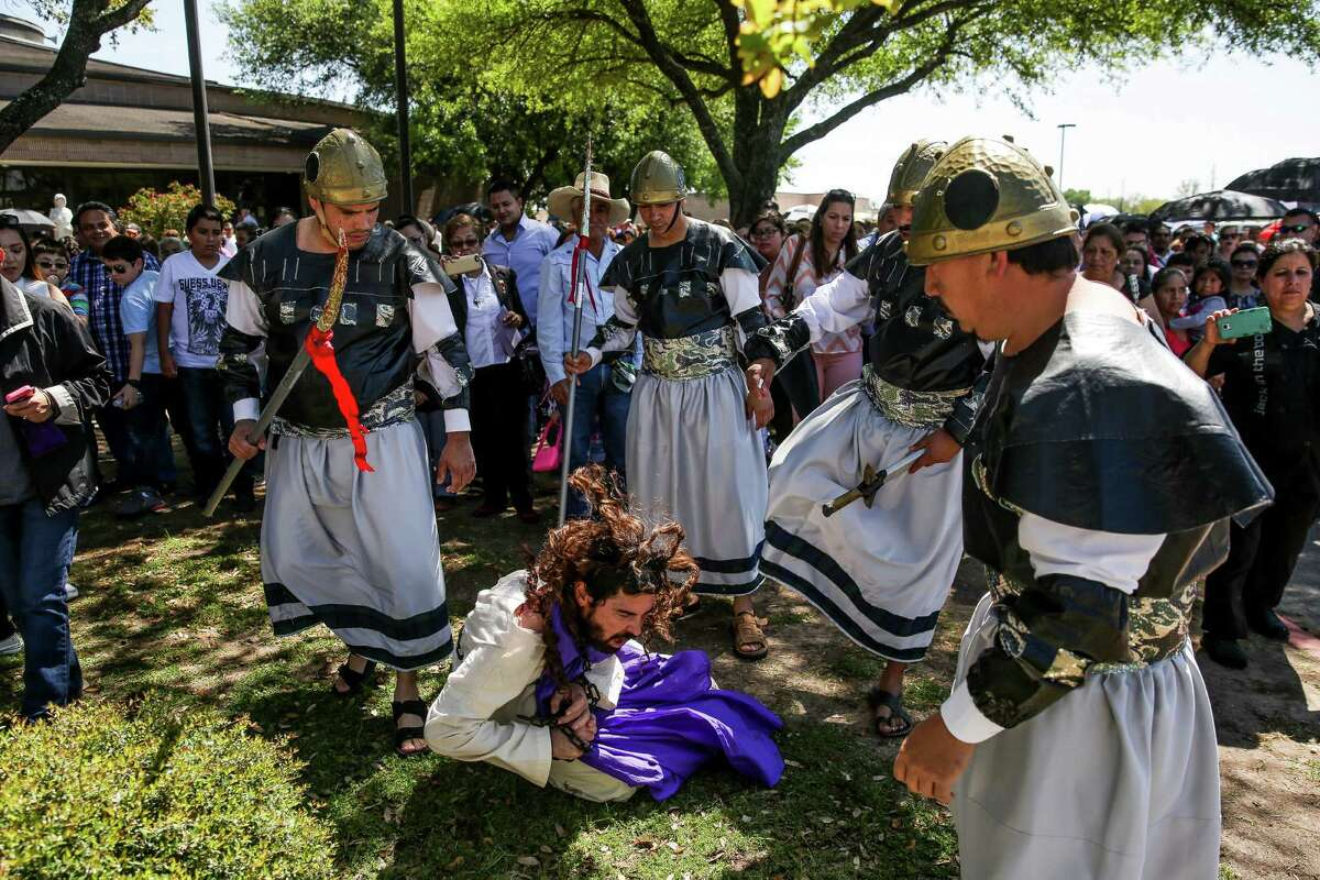 An actor playing Jesus is pushed to the ground by Roman soldiers as he is led to the First Station as a crowd of about 2000 people watches the procession of the Stations of the Cross at the St. Elizabeth Ann Seton Catholic Church and Schools on Good Friday, March 25, 2016 in Houston.