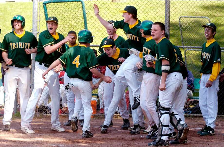 Trinity's players celebrate after Brian O'Neill's grand slam home run in the 9th inning which gave the Crusaders a 7-3 win over Brien McMahon at the Trinity Catholic vs Brien McMahon baseball game at Trinity in Stamford, Conn. on Monday April 12, 2010. Photo: Dru Nadler / Stamford Advocate