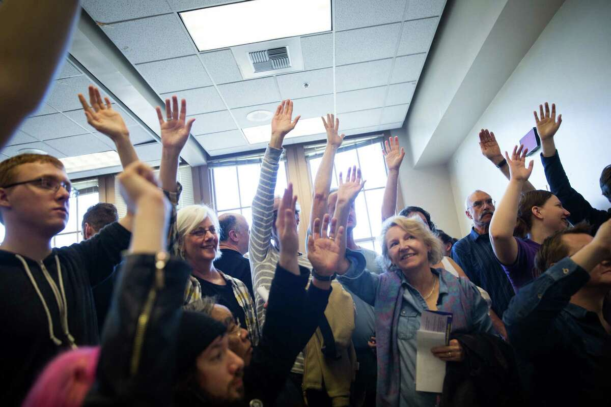 Voters raise their hands in support of democratic presidential candidate Bernie Sanders during the democratic caucus at Tops K-8 School on Saturday, Mar. 26, 2016.